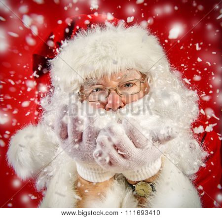 Good old Santa Claus blowing a snow over Christmas red background. Snowfall, snowflakes. The magic of Christmas.