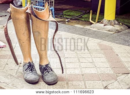 Old prosthetic legs set on a cement floor