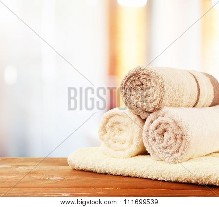 Rolled bath towels on wooden table in bathroom