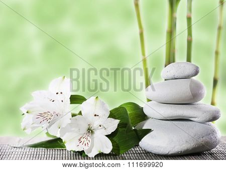 Still life of spa stones on bamboo mat surface with bamboo sticks