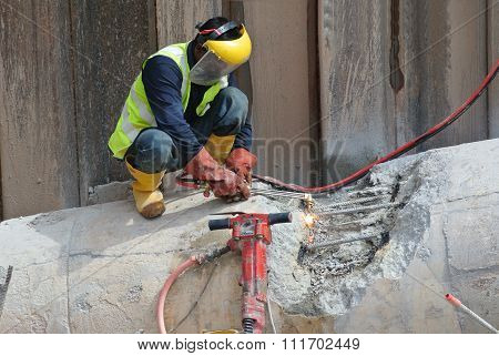 Workers at construction site cutting reinforcement bar using blowtorch