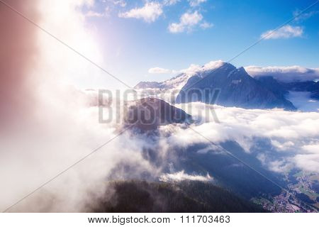 View of the foggy Val di Fassa valley. National Park. Dolomites (Dolomiti), pass Sella. South Tyrol. Location famous resort Canazei, Campitello, Mazzin. Italy, Europe. Dramatic scene. Beauty world.