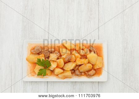 Delicious dish of cooked potatoes with meat on gray wooden background