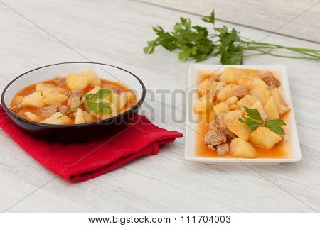 Delicious dishs of cooked potatoes with meat on gray wooden background
