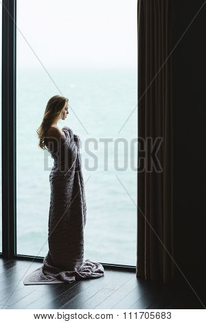 Full length portrait of beautiful thoughtful young female with long hair standing in knitted coverlet