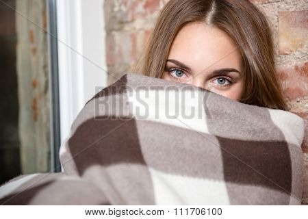 Portrait of a young woman peeking from warm plaid