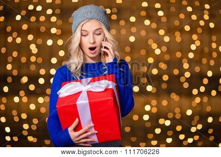 Portrait of a young amazed woman holding present box and talking on the phone over holidays lights background