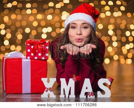Pretty cute young female in santa claus hat sending a kiss and lying near decorated white letters spelling word Xmas over glittering background