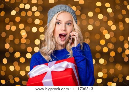 Portrait of a happy surprised woman holding present box and talking on the phone over holidays lights background