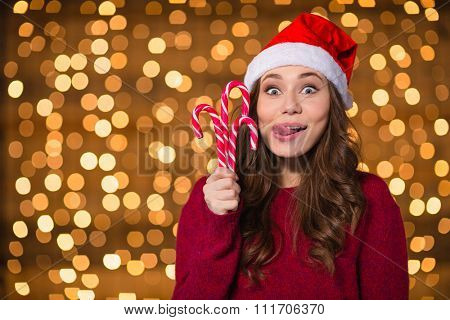 Funny cute girl in santa claus hat with christmas lollypops over shining background