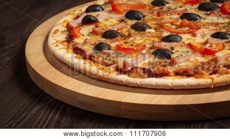 Panoramic image of ham pizza with capsicum and olives on wooden board on table close up
