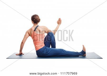 Beautiful sporty fit yogini woman practices yoga asana Marichyasana C - seated spinal twist isolated on white