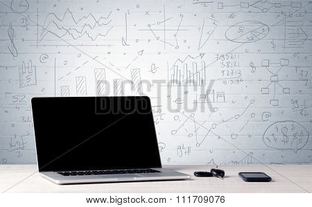 A professional laptop with blank screen sitting on a white office desk in front of wall full of pie charts, calculations and graphs concept
