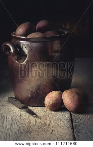Unpeeled Potatoes In A Ceramic Pot With Knife