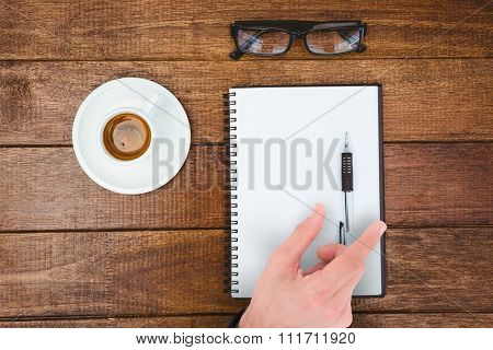 Businessman measuring something with these fingers against above view of business desk