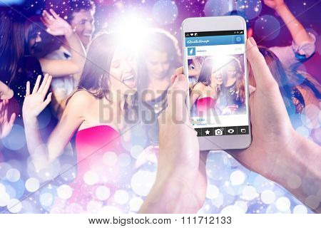 Hand holding smartphone against glowing background