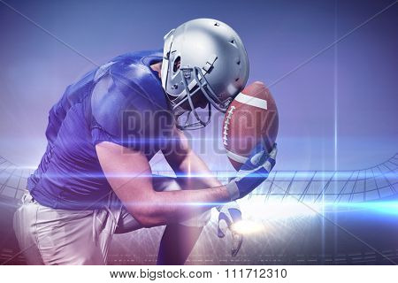 Upset American football player with ball against large football stadium under blue sky