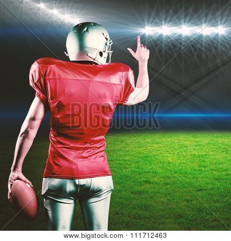 Rear view of American football player pointing while holding ball against rugby stadium