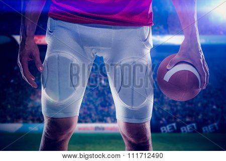 Sports player holding ball against rugby stadium