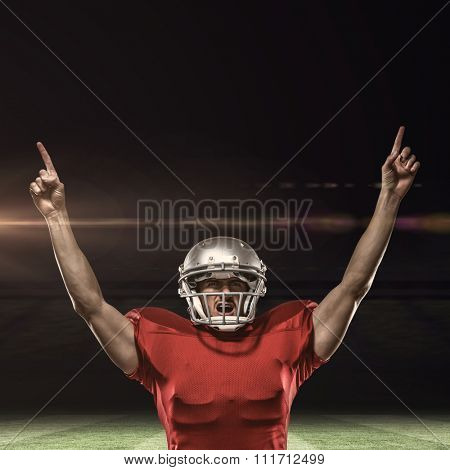 American football player with arms raised standing against rugby pitch