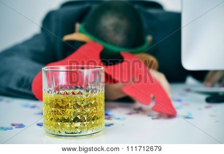closeup of a young caucasian businessman with a reindeer antler headband sleeping at his desk, covered with confetti and with a glass of liquor in the foreground, after an office christmas party