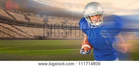 Portrait of American football player running with ball against rugby stadium