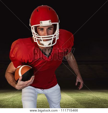 Rugby player with ball posing against football pitch at night