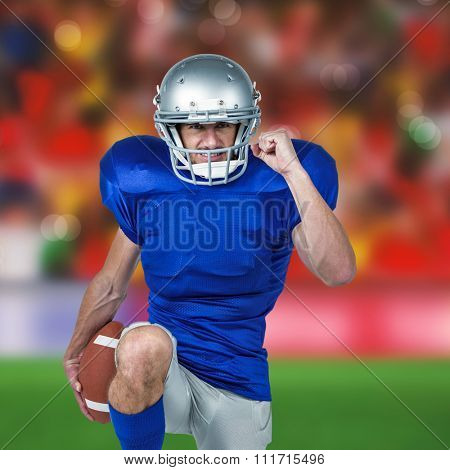American football player standing on one leg while holding ball against blurry football pitch with crowd