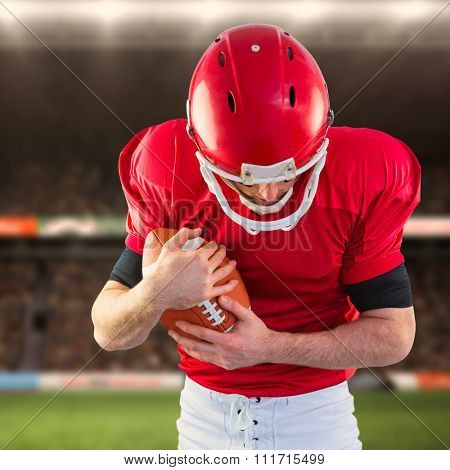 American football player protecting football against rugby fans in arena