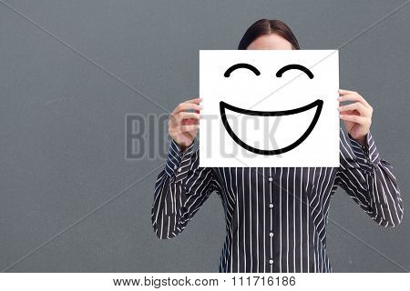 Smiling woman showing a big business card in front of her face against grey background