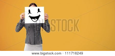 Businesswoman showing a white card in front of her face against yellow
