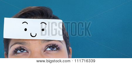 Beautiful woman with blank note on forehead against blue background