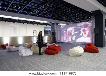 ST. PETERSBURG, RUSSIA - DECEMBER 13, 2015: Girl watch the video installation of AES+F group Inverso Mundus in the central exhibition hall Manege during 4th St. Petersburg International Cultural Forum