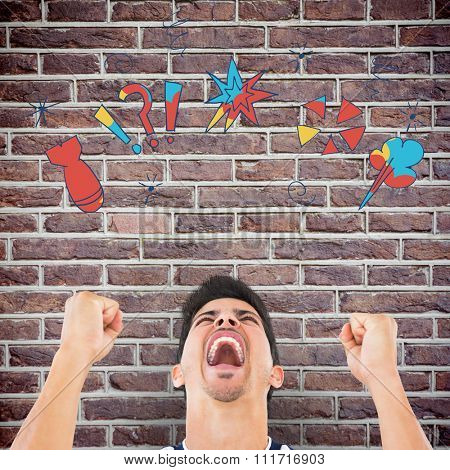 Football player screaming while clenching fists against red brick wall