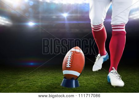 American football player being about to kick football against american football arena