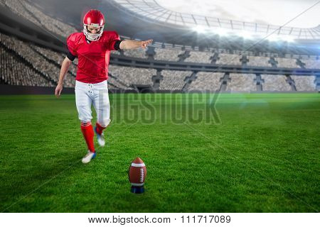 American football player kicking football against rugby stadium