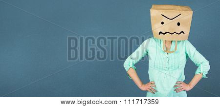 Woman with hands on hip and covering head with brown paper bag against blue background