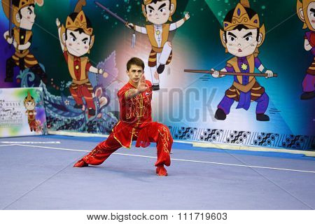 JAKARTA, INDONESIA - NOVEMBER 17, 2015: Pavel Muratov of Russia performs the movements in the men's Compulsory Changquan event at the 13th World Wushu Championship 2015 in Istora Senayan Stadium.