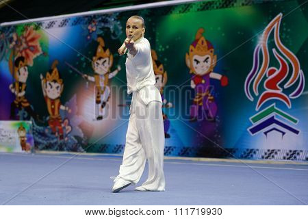 JAKARTA, INDONESIA - NOVEMBER 17, 2015: Daria Tarasova of Russia performs the movements in the women's Gunshu event at the 13th World Wushu Championship 2015 in Istora Senayan Stadium.