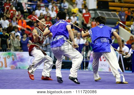 JAKARTA, INDONESIA - NOVEMBER 17, 2015: The Thailand men's duel team performs the action fights in the Men's Duel event at the 13th World Wushu Championship 2015 in Istora Senayan Stadium.