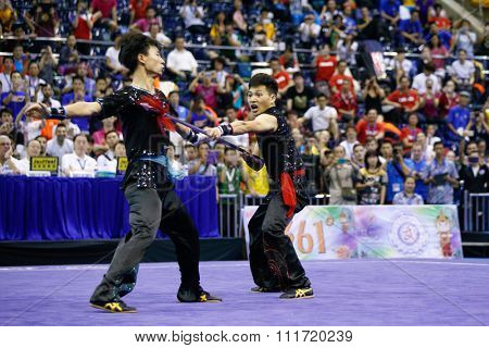 JAKARTA, INDONESIA - NOVEMBER 17, 2015: The China team performs the action fights in the Men's Duel event at the 13th World Wushu Championship 2015 in Istora Senayan Stadium.