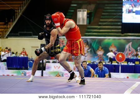 JAKARTA, INDONESIA - NOVEMBER 17, 2015: Domenico Stabile of Italy (red) fights Georges Eid of Lebanon in the men's 80kg Sanda semi-final event at the 13th World Wushu Championship 2015.