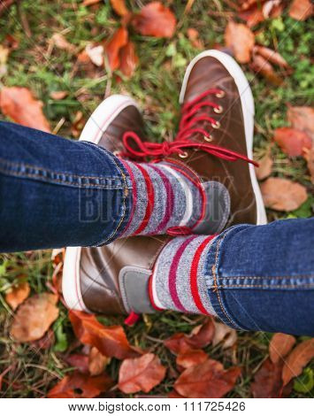 a pair of legs with casual brown leather boots and striped socks on with leaves and grass as a background for an instagram look