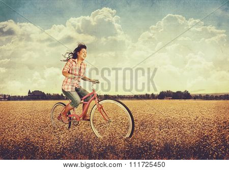 a pretty girl riding her bike in a field full of yellow flowers toned with a retro vintage instagram filter app or action effect