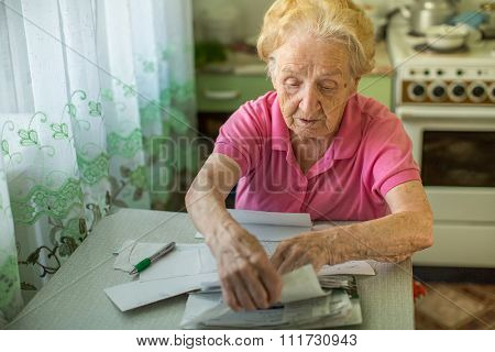 An elderly woman fills in for the payment of utilities.