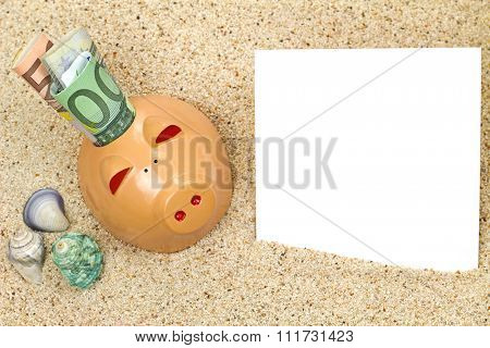 An orange piggy bank with rolled money on beach sand next to sea shells and a blank white paper