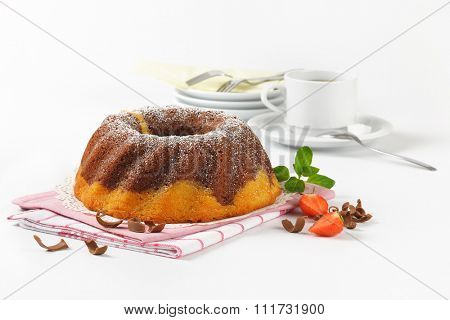 marble bundt cake and cup of coffee on white background