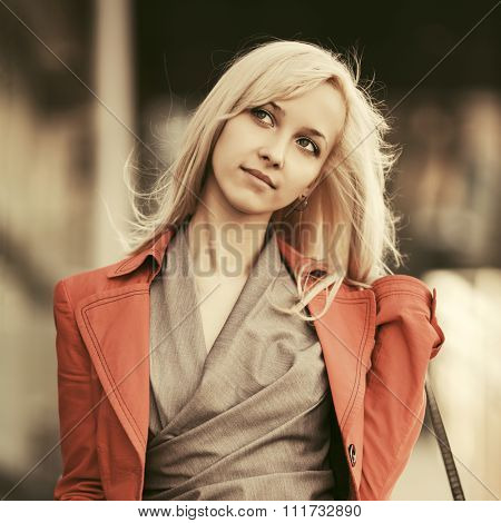 Young fashion business woman in red jacket walking on city street