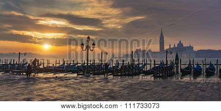 Gondolas by Saint Mark square during sunrise with San Giorgio di Maggiore church in the background in Venice Italy