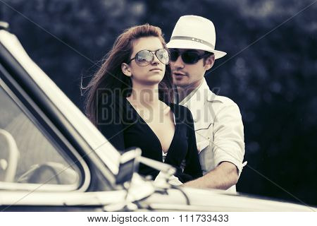 Young fashion couple in love by retro car